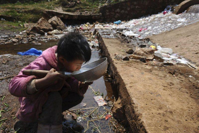 Enfant qui boit dans une évacuation eaux usées