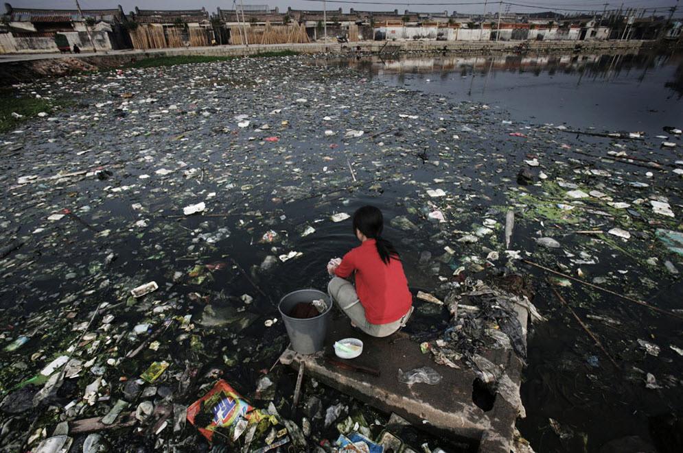 Une femme fait sa lessive dans un étang pollué