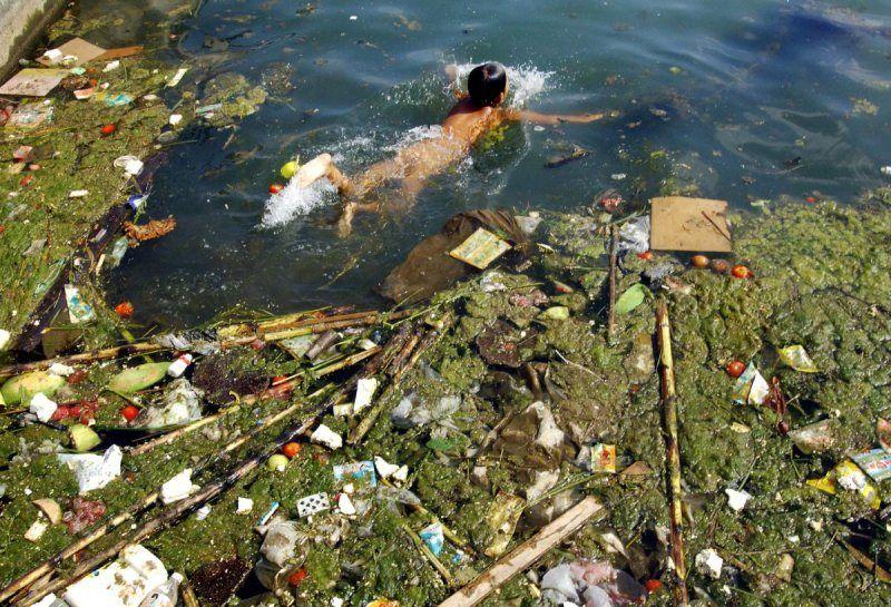 enfant nage dans eau polluée d'un réservoir à pinga