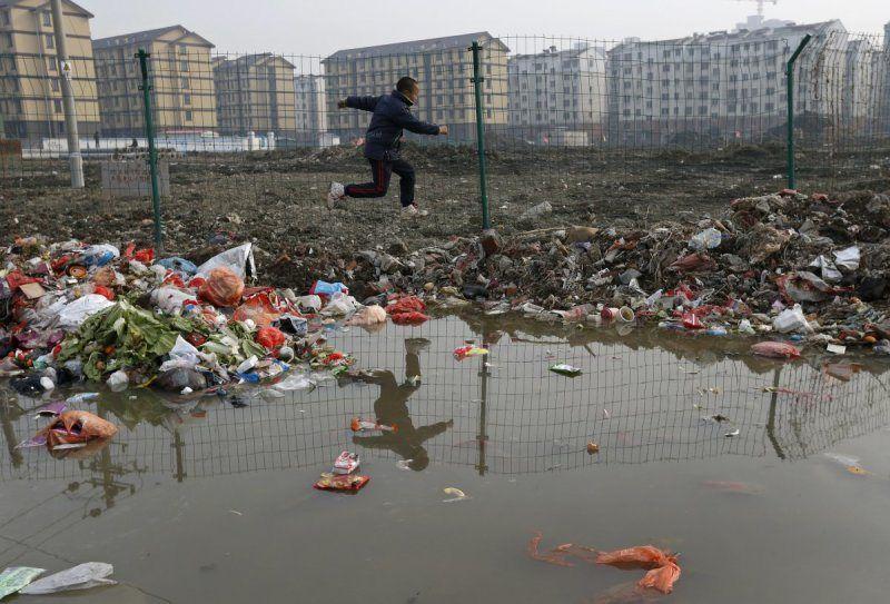 enfant qui saute une flaque d'eau polluée